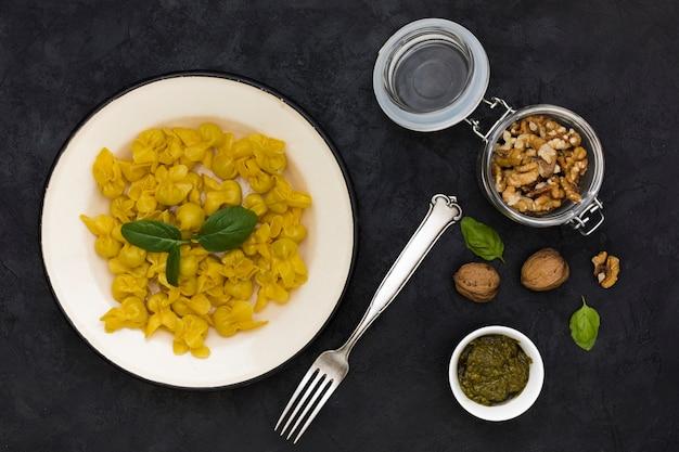 Pasta di tortellini cotto con foglie di basilico e ingredienti su sfondo nero