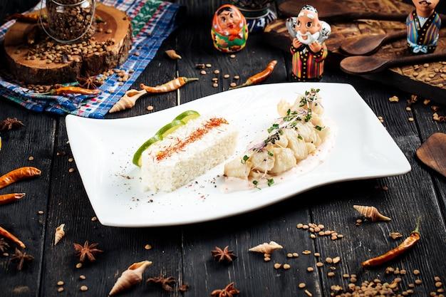 Приготовленное филе белой рыбы с рисом на черном деревянном столе
