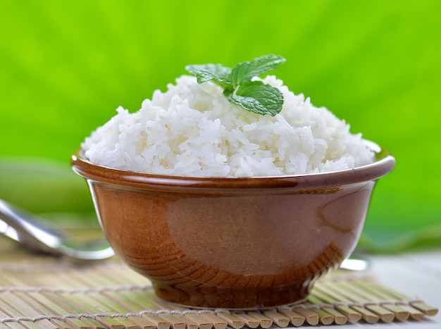 Cooked white rice garnished with mint in a ceramic bowl
