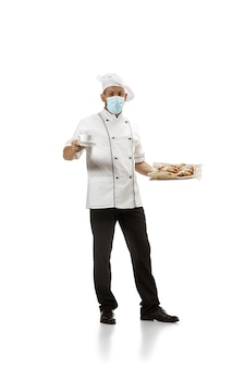 Повар, шеф-повар, пекарь в маске для лица в униформе на белом фоне с круассанами. молодой человек, портрет повара ресторана. бизнес, foor, профессиональная деятельность, концепция эмоций. copyspace для рекламы.