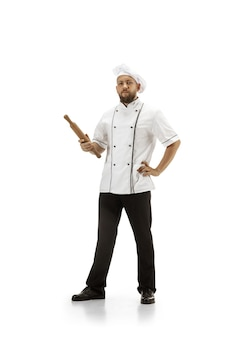Cooker, chef, baker in uniform isolated on white studio background, gourmet. young man, restaurant cooker's portrait. business, foor, professional occupation, emotions concept. copyspace for ad.