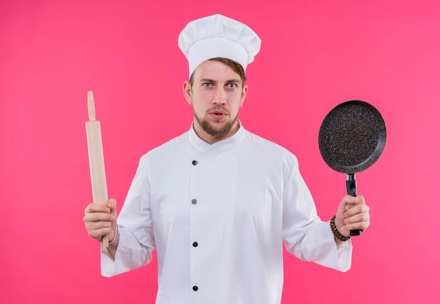 ピンクの壁の上に立っているめん棒と鍋で顔にカメラショックを探している炊飯器