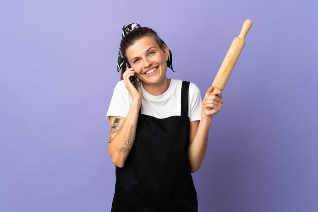 Кухарка словацкая женщина изолирована на фиолетовом фоне, ведя разговор по мобильному телефону с кем-то