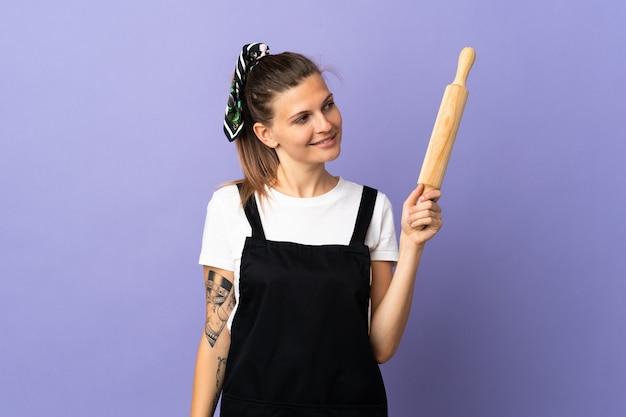 横を見て笑って紫色の背景に分離された炊飯器スロバキア女性