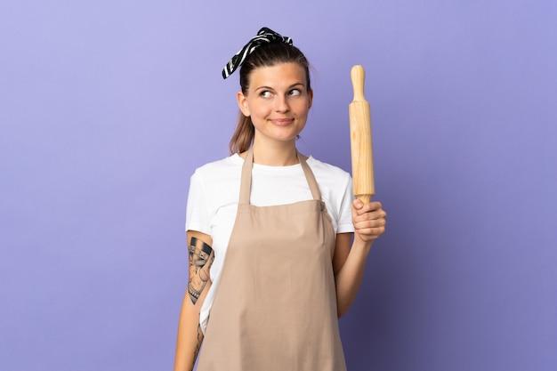 Кухарка словацкая женщина изолирована на фиолетовом фоне, делая жест сомнения, глядя в сторону