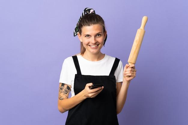 Кухарка словацкая женщина изолирована на фиолетовом фоне, отправляя сообщение с мобильного телефона
