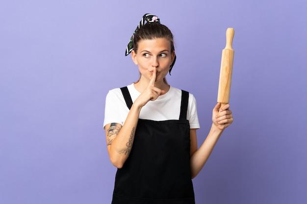 쿠커 슬로바키아어 여자는 입에 손가락을 넣어 침묵 제스처의 표시를 보여주는 보라색 배경에 고립