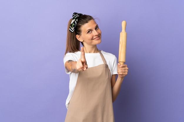 쿠커 슬로바키아어 여자는 보라색 배경에 표시하고 손가락을 들어 올려