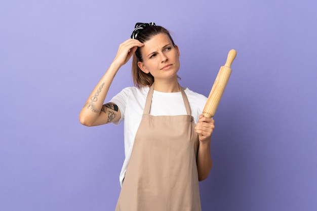 Cooker slovak woman isolated on purple background having doubts while scratching head