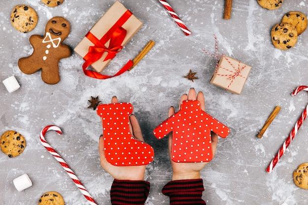 Куки в форме свитера и носка лежат в руках над декором chirstmas
