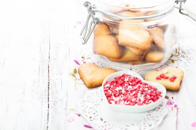 テーブルの上のガラスの瓶にハート型のバレンタインの装飾としてのクッキー