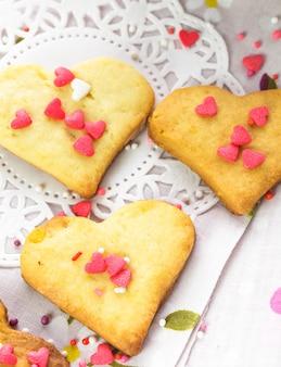 テーブルの上のハート型のバレンタインの装飾としてのクッキー