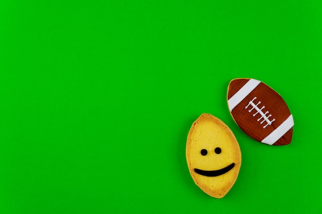Cookie as an american football ball isolated on green background. top view.