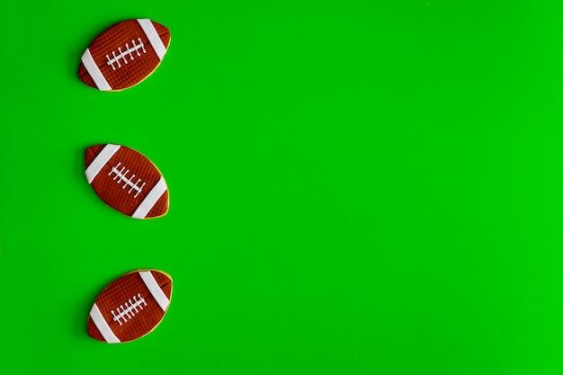 緑の背景に分離されたアメリカンフットボールのボールとしてのクッキー。上面図。
