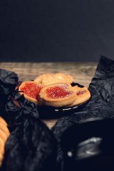 クッキー、ビスケットは黒いテーブルの背景に赤いラズベリージャムでいっぱい。トップビュー、コピースペース。
