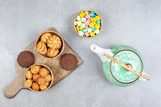 Cookie bowls on wooden board next to ornate teapot and bowl of candies on marble background. high quality photo