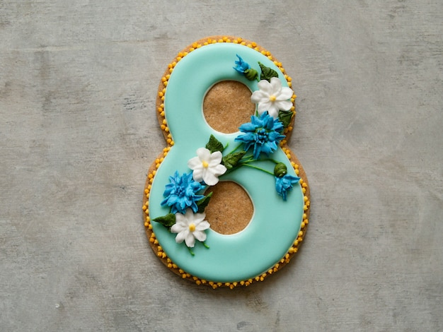 Cookie covered with blue glaze made in a form of number eight with flowers - cornflowers and daisies - on gray background