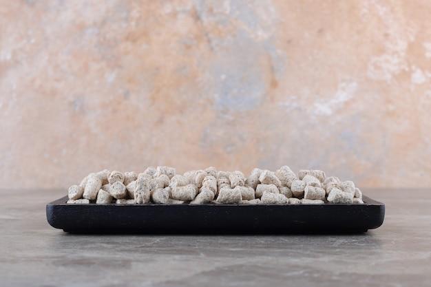Крошки печенья в подносе, на мраморной поверхности