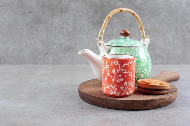 Un biscotto, una tazza di tè e una teiera sulla tavola di legno su fondo di marmo. foto di alta qualità