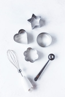 Cookie cutters, kitchen accessories on a white kitchen table