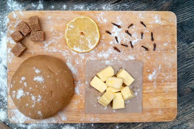 Cookie dough. on the kitchen table. ingredients - butter, lemon, flour, sugar, cloves.