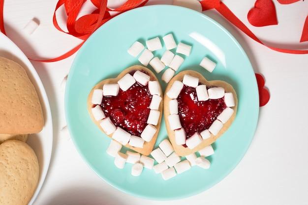 Печенье сердце украшено вареньем и зефиром на день святого валентина, крупным планом, выпечка на праздник. декоративные сердца вид сверху.
