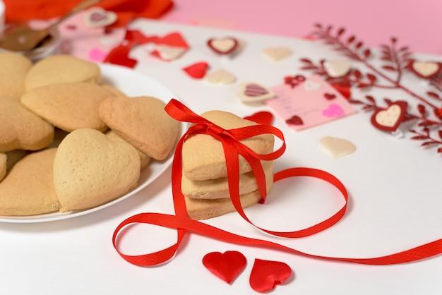 Печенье сердце, перевязанное красной лентой на день святого валентина, выпечка к празднику. декоративные сердца вид сверху.