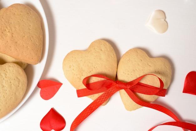 Печенье сердце перевязано красной лентой на день святого валентина, крупным планом, выпечки на праздник. декоративные сердца вид сверху.