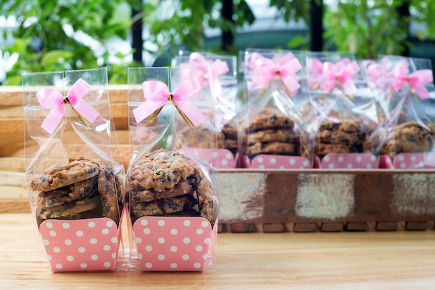 Cookie in plastic bag on wooden background with ribbon bow tie
