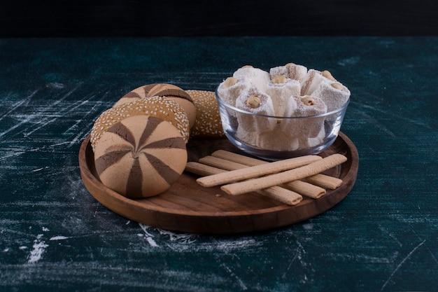Piatto per biscotti con panini, lokum in una tazza di vetro e bastoncini di cialda al centro