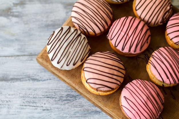 나무 보드에 쿠키 샌드위치입니다. 윤이 난 비스킷의 상위 뷰입니다. 패스트리 카페에서 부시 케이크. 손님을 위한 최고의 대접.