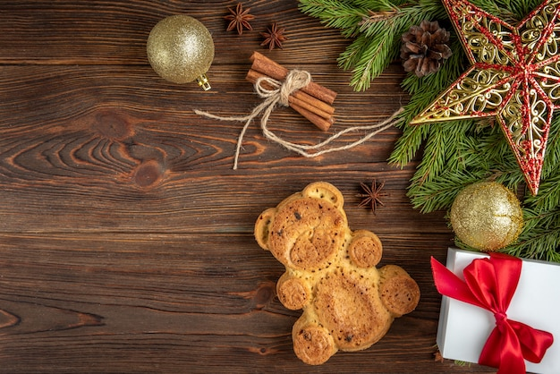 Cookie in the shape of a bear on wooden with christmas balls