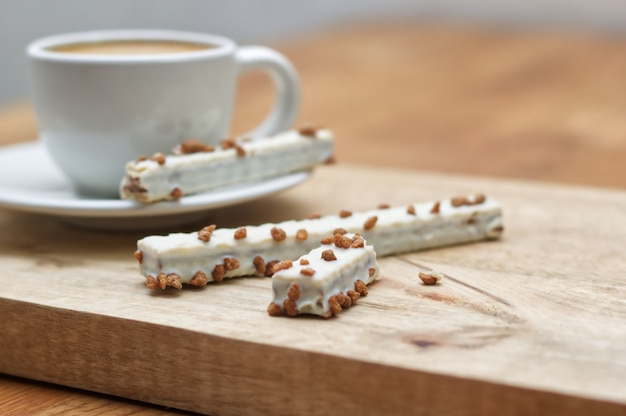 Cookie wafers in glaze and cup of coffee on a wooden table
