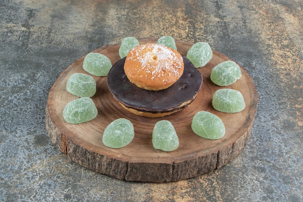Cookie with chocolate and marmalade candies on wooden piece
