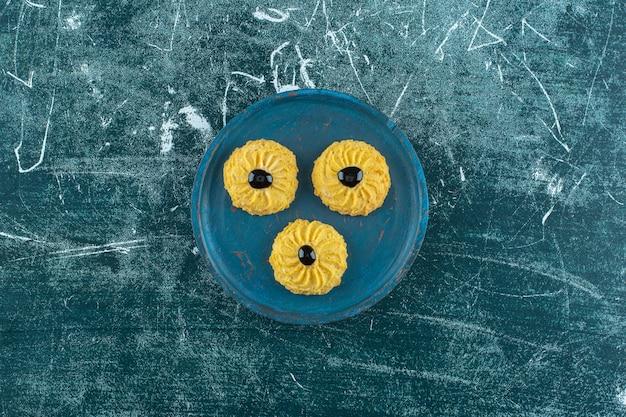 Печенье с шоколадом на деревянной тарелке, на синем фоне. фото высокого качества