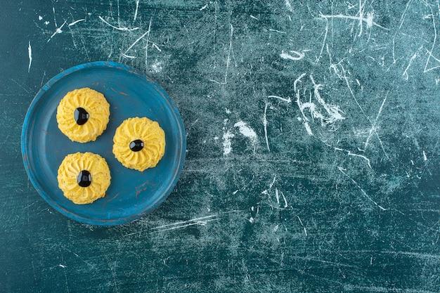 青い背景に、木の板にチョコレートとクッキー。高品質の写真
