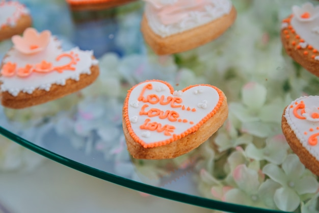 Cookie with glaze lettering love lies on the glass table