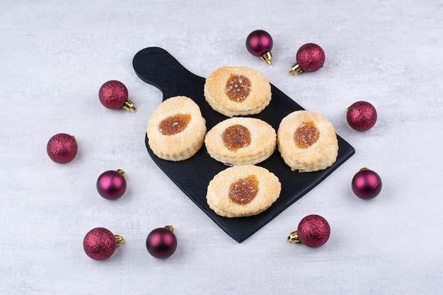 Печенье с вареньем на черной доске с блестящими шариками. фото высокого качества