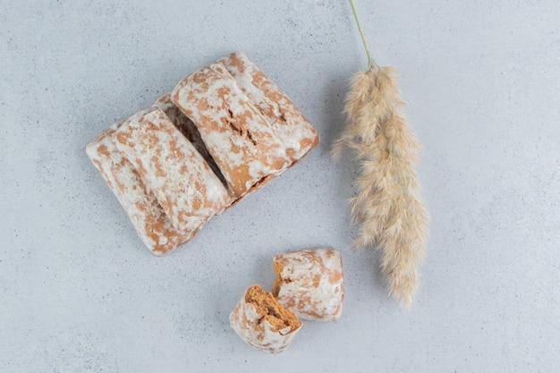 Confezioni di biscotti impacchettati insieme accanto a un gambo di erba piuma su sfondo di marmo.