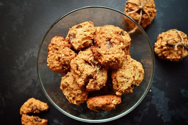 チョコレートとオートミールクッキー。分離された黒いテーブル背景にクッキー。コード付きのcookieのスタック。