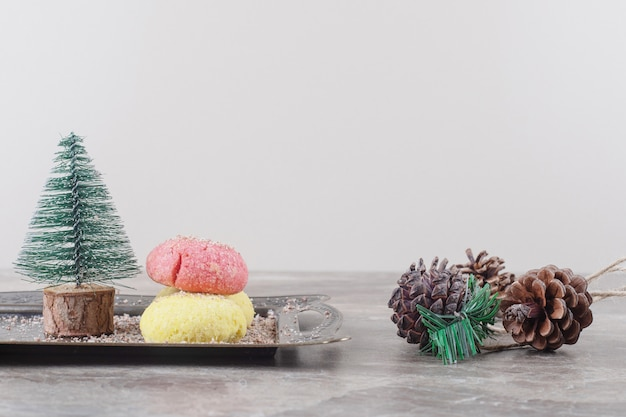 Печенье и фигурка дерева на подносе рядом с сосновыми шишками на мраморе