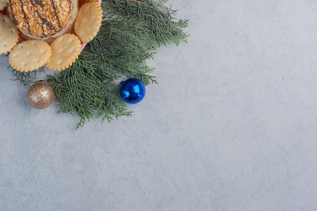 大理石の表面のクリスマスの装飾の中でボウルにクッキーとビスケット