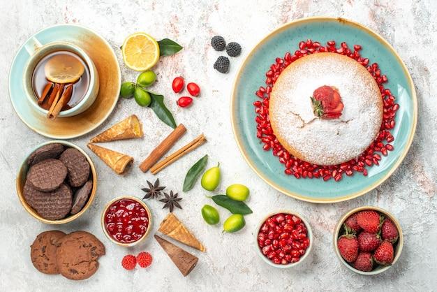 クッキーとケーキベリーとケーキクッキーシナモンスティックとお茶のカップ