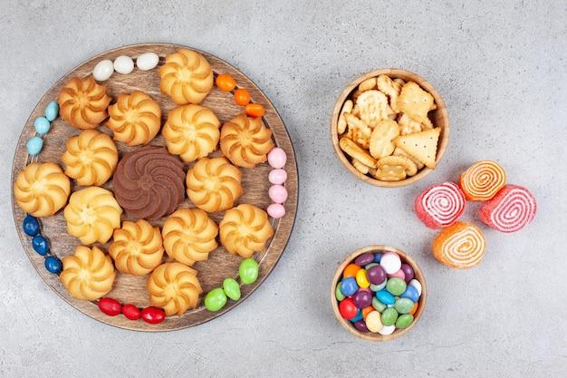 Печенье и конфеты на деревянной доске и в деревянных мисках с мармеладом на мраморном фоне. фото высокого качества