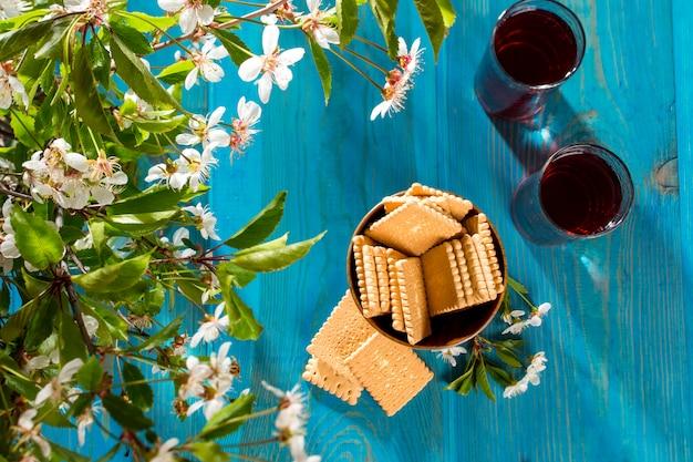 花の隣のテーブルにクッキーとチェリージュース