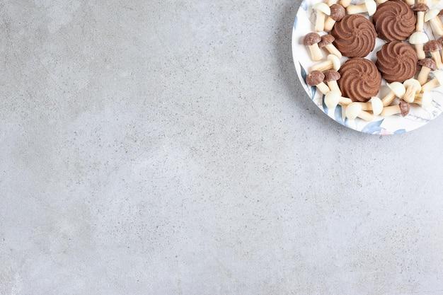대리석 배경에 접시에 쿠키와 초콜릿 버섯. 고품질 사진