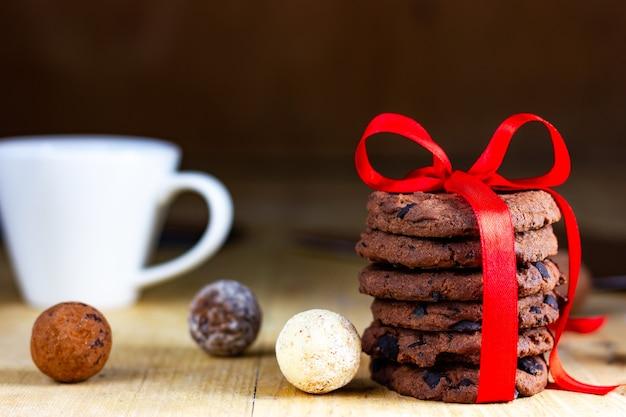 Печенье и шоколадные трюфели, перевязанные красной праздничной лентой.