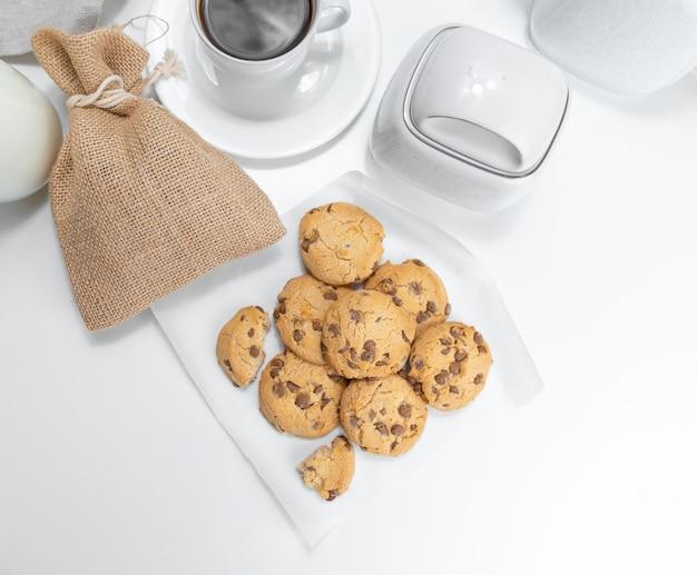 白いテーブルの上のクッキーと一杯のコーヒー