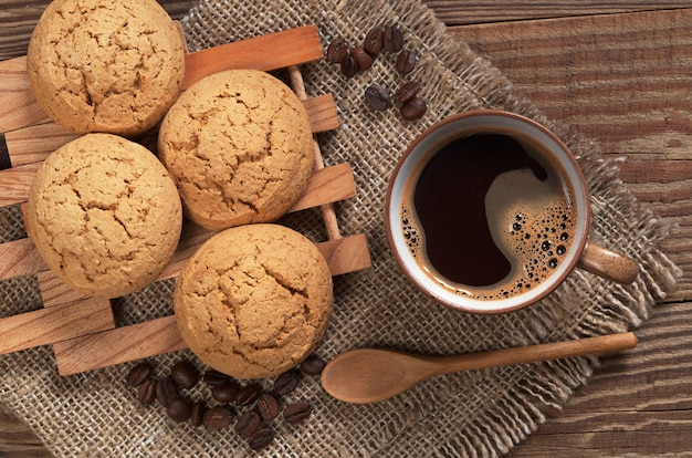 Печенье и чашка кофе на деревянном столе крупным планом