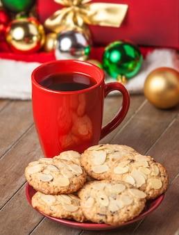 쿠키와 배경에 크리스마스 선물이 있는 커피 한 잔